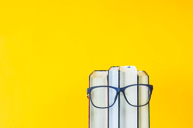Uma pilha de livros com óculos é uma imagem do rosto de uma pessoa