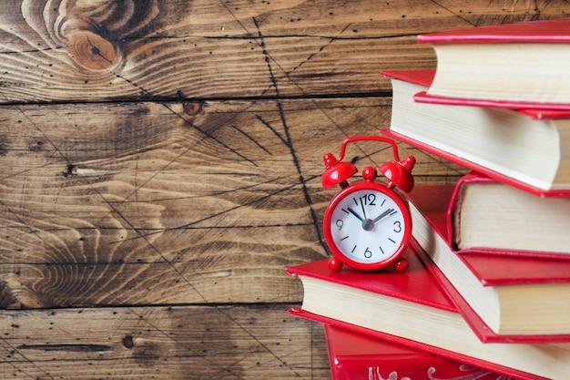 Uma pilha de livros de capa dura e um despertador em uma mesa de madeira. copie o espaço para texto