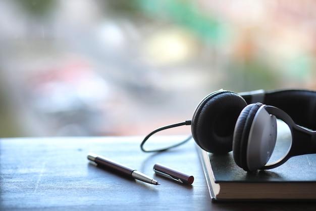 Uma pilha de livros didáticos com fones de ouvido pretos em uma mesa