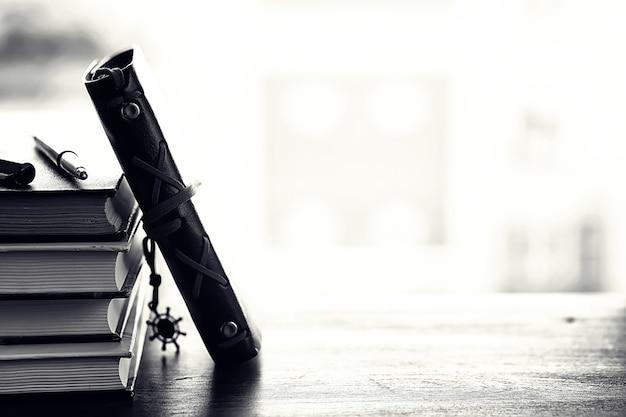Uma pilha de livros didáticos no parapeito da janela e utensílios de escrita