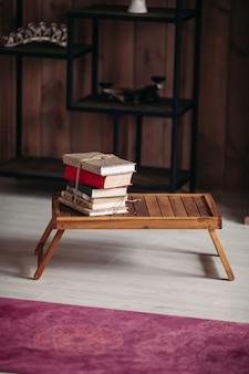Uma pilha de livros diferentes em uma pequena mesa de madeira na sala iluminada perto do tapete roxo