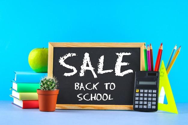 Uma pilha de livros e artigos de papelaria em um fundo de quadro-negro. mesa de trabalho, educação, escola. venda.