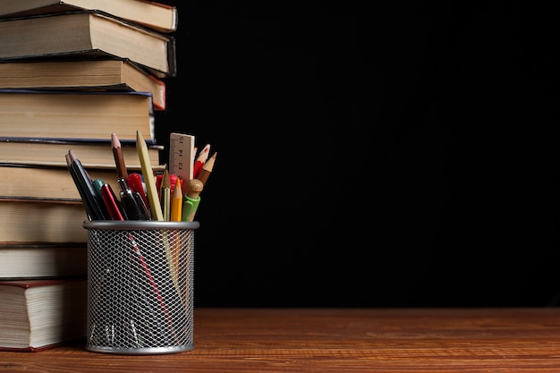 Uma pilha de livros e um suporte para canetas sobre uma mesa, sobre um fundo preto.