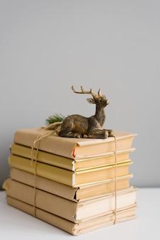 Uma pilha de livros em uma capa de artesanato, amarrada com barbante, nos livros é uma estatueta de um cervo sentado