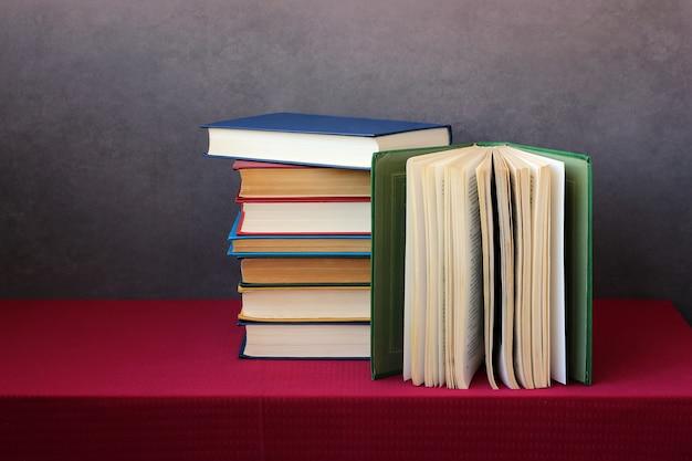 Uma pilha de livros nas capas coloridas sobre a mesa com toalha de mesa vermelha.