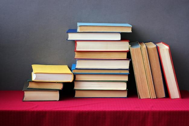 Uma pilha de livros nas capas coloridas sobre a mesa com uma toalha de mesa vermelha. ainda vida com livros.