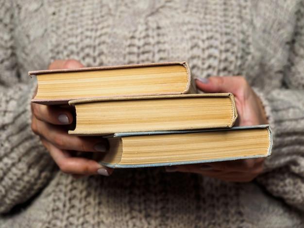 Uma pilha de livros nas mãos da mulher