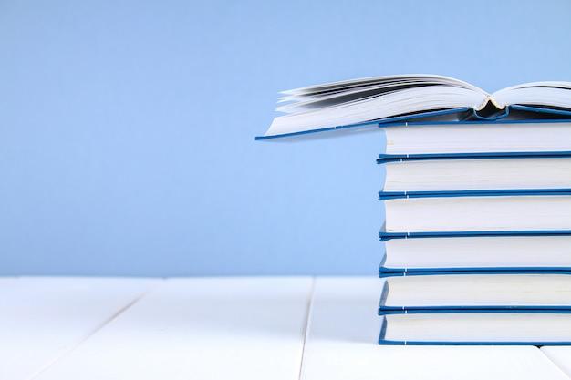 Uma pilha de livros sobre um fundo azul. um livro escondido no topo da pilha