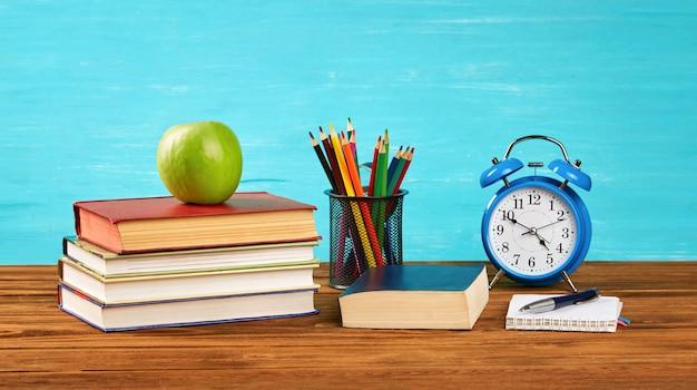 Uma pilha de livros, um despertador, um livro aberto, lápis de cor, uma maçã verde na mesa.