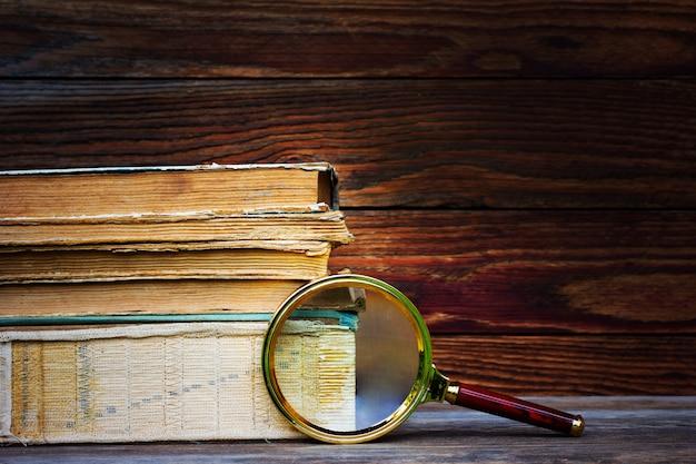 Uma pilha de livros velhos e de lente de aumento no fundo de madeira.