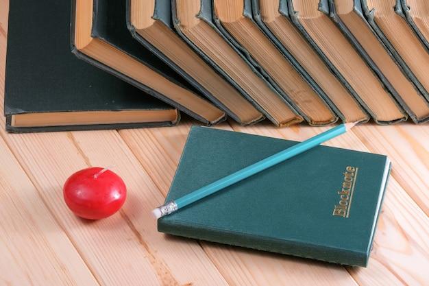 Uma pilha de livros velhos e esfarrapados com encadernações verdes idênticas está sobre uma mesa de madeira ao lado de um caderno