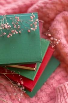 Uma pilha de livros vermelhos e verdes com flores secas em um suéter de malha rosa quente