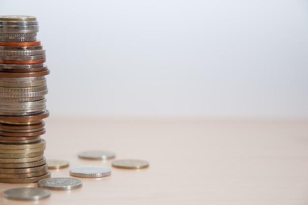 Uma pilha de moedas de diferentes países, cor, dignidade e tamanho à esquerda na borda da imagem.