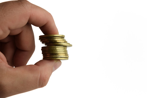 Uma pilha de moedas de ferro amarelas presas com dois dedos em um fundo branco