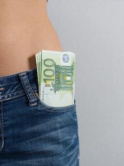 Uma pilha de notas de cem euros sobressai do bolso da frente da calça jeans feminina.