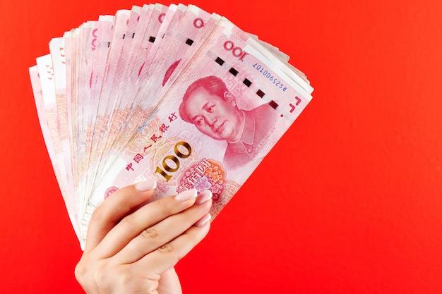Uma pilha de notas de rmb de dinheiro yuan chinês em uma mão feminina em um vermelho