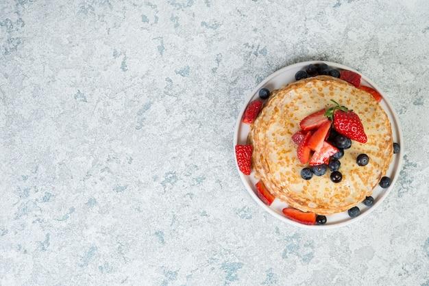 Uma pilha de panquecas caseiras finas encontra-se em um prato, decorado com frutas e mel, sobre um fundo cinza de concreto, close-up, cópia espaço