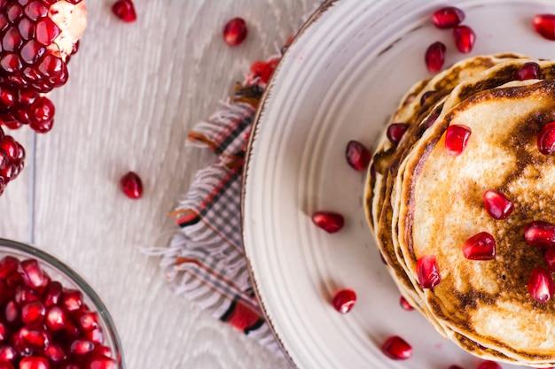Uma pilha de panquecas com sementes de romã em um prato