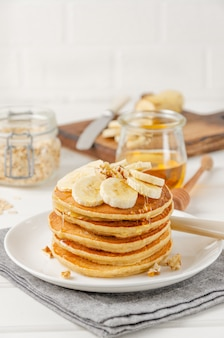 Uma pilha de panquecas de aveia e banana com fatias de bananas frescas, nozes e mel com uma xícara de chá