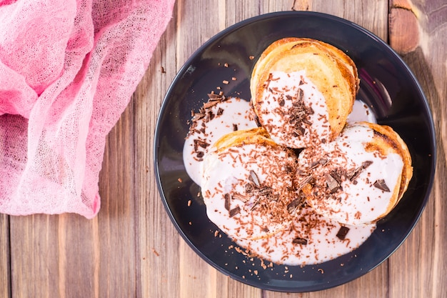 Uma pilha de panquecas recheadas com iogurte de frutas e polvilhadas com chocolate ralado em um prato sobre uma mesa de madeira