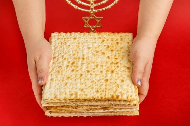 Uma pilha de pão ázimo nas mãos femininas em uma superfície vermelha perto da menorá Foto Premium