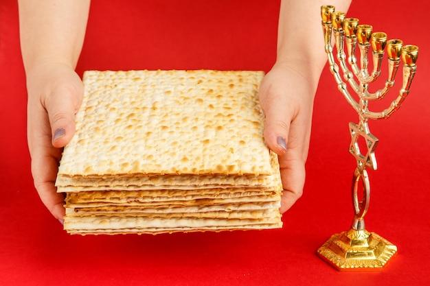 Uma pilha de pão ázimo nas mãos femininas em uma superfície vermelha perto da menorá