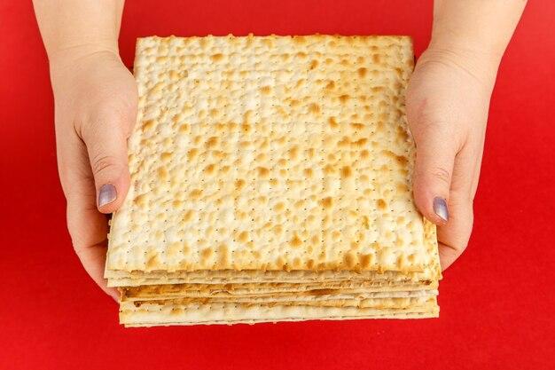Uma pilha de pão ázimo nas mãos femininas em uma superfície vermelha