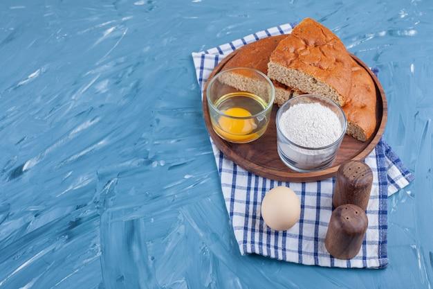Uma pilha de pão fatiado em uma placa ao lado de ovo e farinha em um pano de prato, na mesa azul.