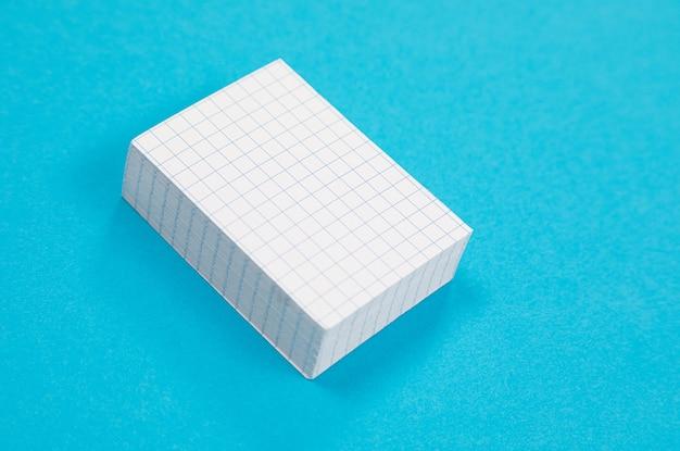 Uma pilha de papel de rascunho branco está deitado na superfície azul isolada