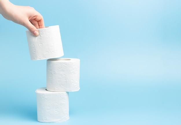 Uma pilha de papel higiênico branco sobre fundo azul, copie o espaço.