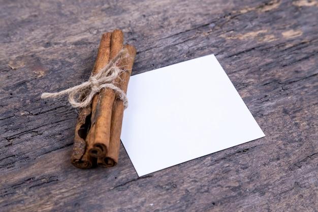 Uma pilha de paus de canela e um pedaço de papel na mesa de madeira velha com espaço de cópia. idéia de cartão de natal