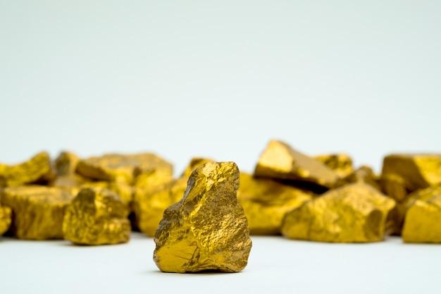 Uma pilha de pepitas de ouro ou minério de ouro isolado no fundo branco, pedra preciosa ou pedaço de pedra dourada