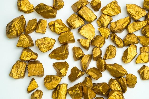 Uma pilha de pepitas de ouro ou minério de ouro sobre fundo branco, pedra preciosa ou pedaço de pedra dourada