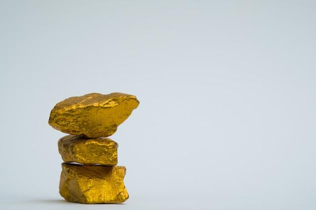 Uma pilha de pepitas de ouro ou minério de ouro sobre fundo branco,