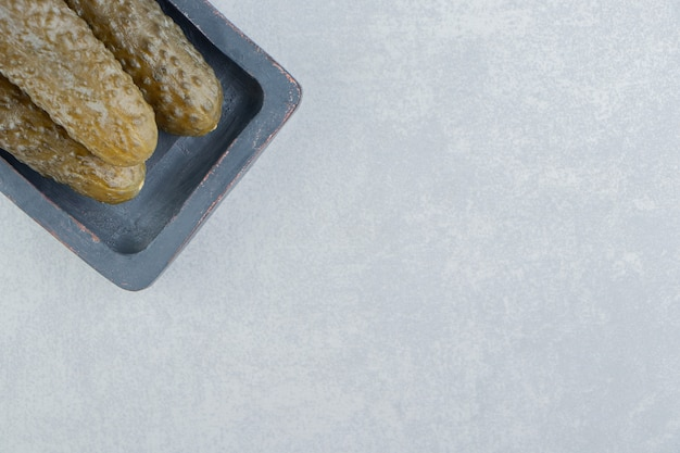 Uma pilha de picles de pepino em uma placa, na superfície de mármore
