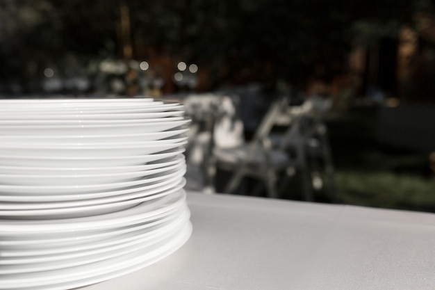 Uma pilha de pratos brancos limpos está em uma mesa com uma toalha de mesa branca ao ar livre