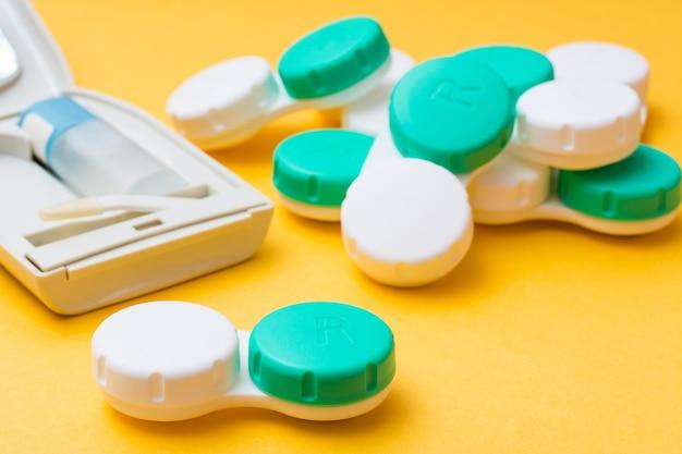 Uma pilha de recipientes para armazenar lentes de contato e um estojo para acessórios em um fundo amarelo