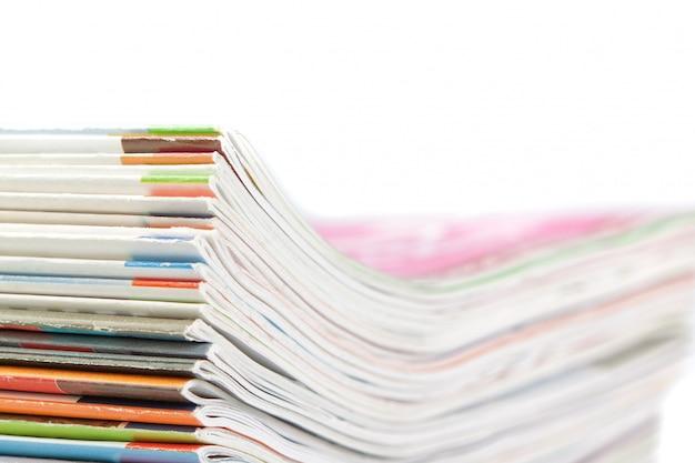 Uma pilha de revistas em uma parede branca. fechar-se.