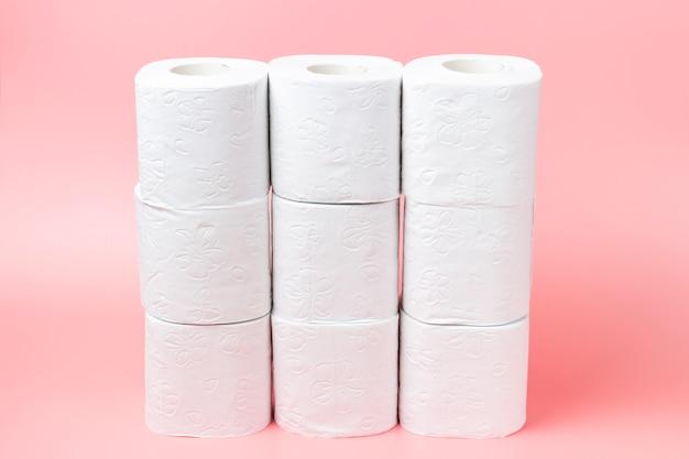 Uma pilha de rolos brancos em papel higiênico em um fundo rosa close-up, comprando concerto