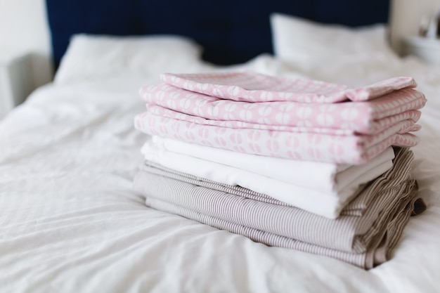 Uma pilha de roupa limpa e passada na cama