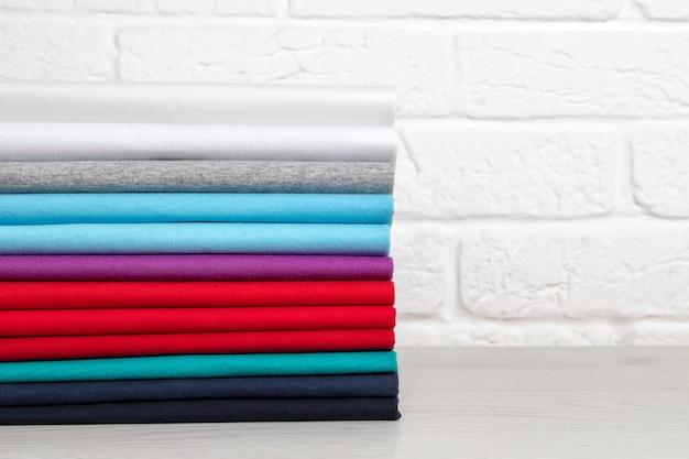 Uma pilha de roupas coloridas limpas e cuidadosamente dobradas sobre uma mesa de madeira clara. cores do arco-íris. lugar para texto
