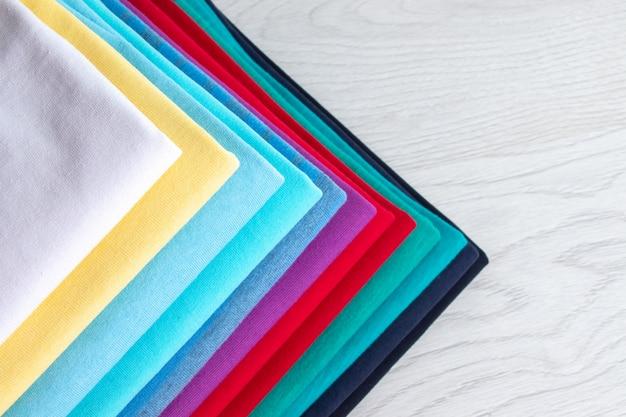 Uma pilha de roupas coloridas limpas e cuidadosamente dobradas sobre uma mesa de madeira clara. cores do arco-íris.
