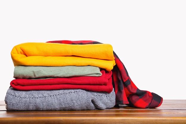 Uma pilha de roupas de inverno outono dobradas em uma mesa de madeira com fundo branco.