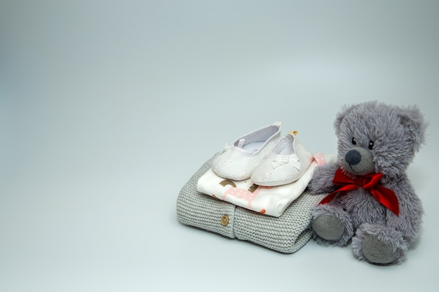 Uma pilha de roupas e acessórios de bebê com ursinho de pelúcia