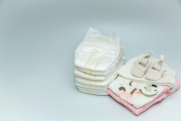 Uma pilha de roupas e acessórios de bebê.