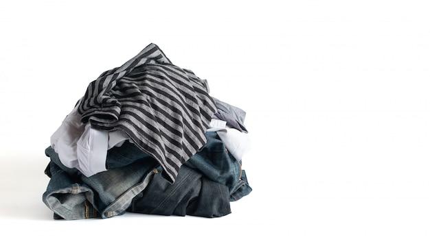 Uma pilha de roupas e calça jeans desbotada, isolado no fundo branco com traçado de recorte
