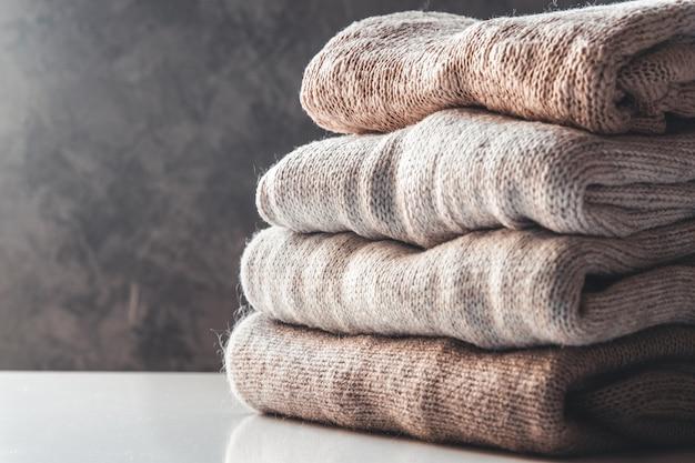 Uma pilha de suéteres de malha, o conceito de calor e conforto, passatempo, plano de fundo, closeup