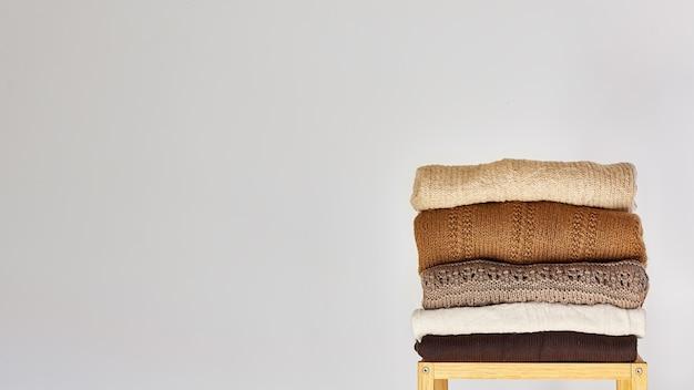 Uma pilha de suéteres de malha quentes com diferentes padrões de tricô em fundo cinza claro.