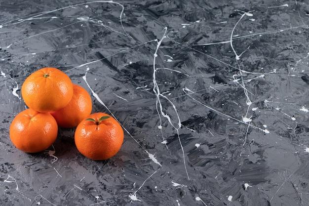 Uma pilha de tangerina fresca, na mesa mista.