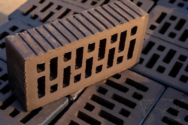 Uma pilha de tijolos vazados marrom-escuros em uma construção ao pôr do sol